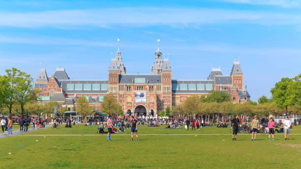 Rijksmuseum w Holandi Amsterdam, Netherlands - March 31, 2016: Panoramic banner background with people, grass field and view of Rijksmuseum, Museumplein museumplein stock pictures, royalty-free photos & images
