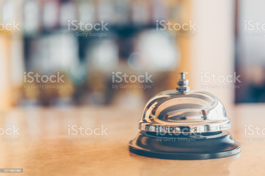 Ring bell for staff calling on the stand. Reception and bar background. Holiday and travel concept Ring bell for staff calling on the stand. Reception and bar background. Holiday and travel concept. Horizontal, selective cold toning Backgrounds Stock Photo