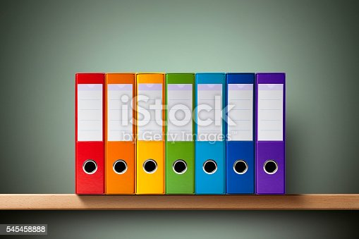 Seven ring binders on the shelf.
