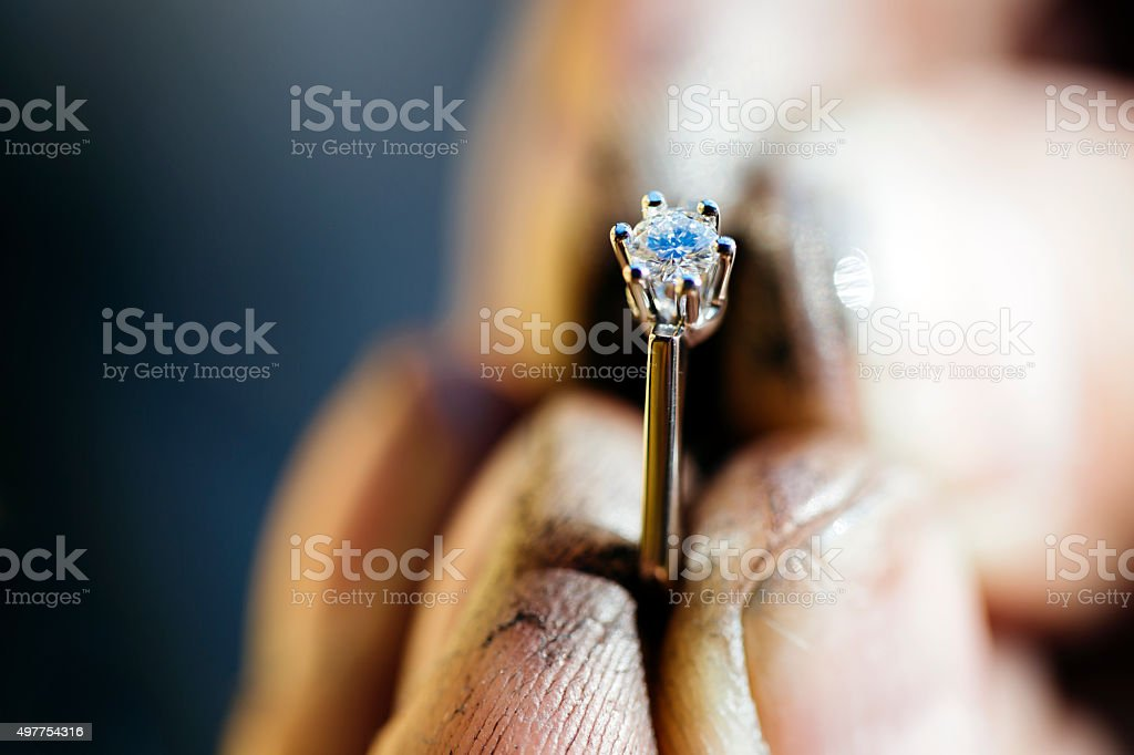 Ring held by jeweler after polishing stock photo