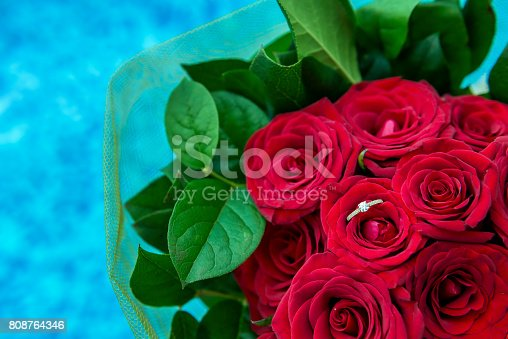 Horizontal color close-up image of diamond gold ring hide in bouquet of red roses.