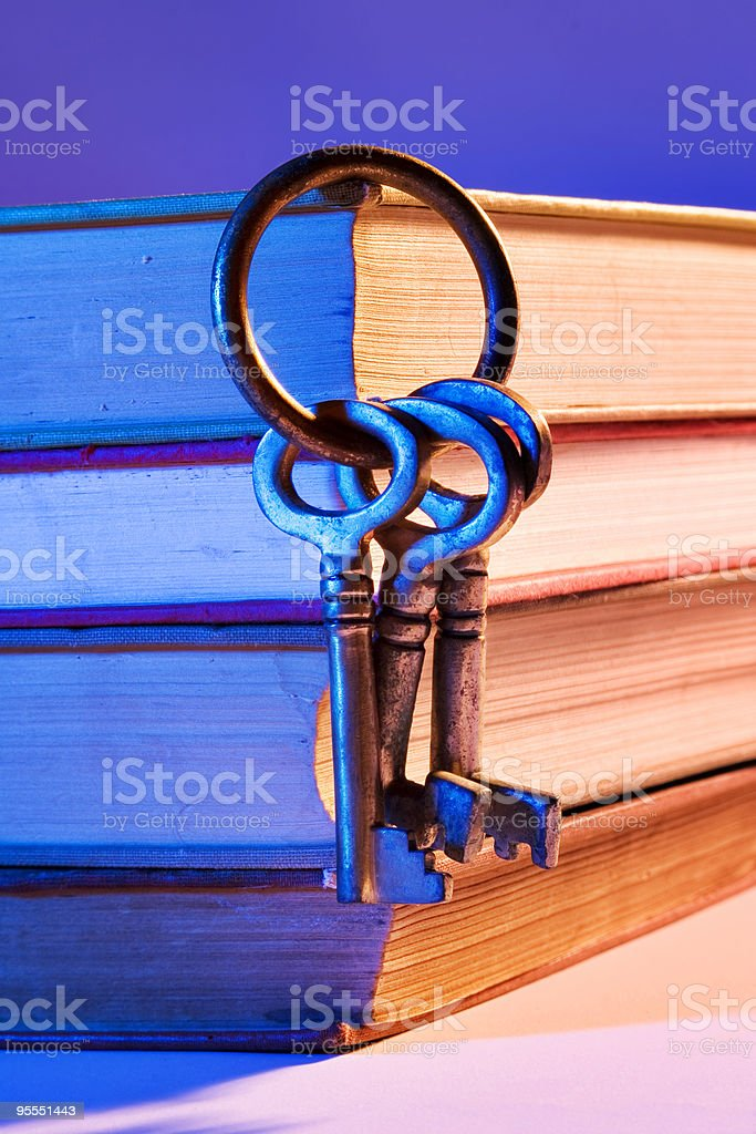 Ring of keys hanging from a pile of hardback books stock photo
