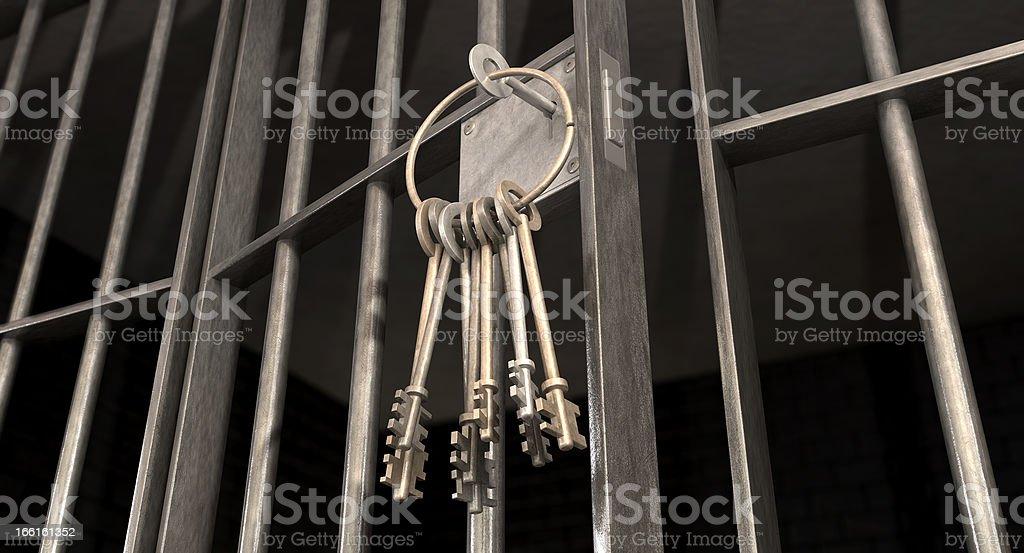 Ring of keys hanging from a slightly ajar jail cell door stock photo