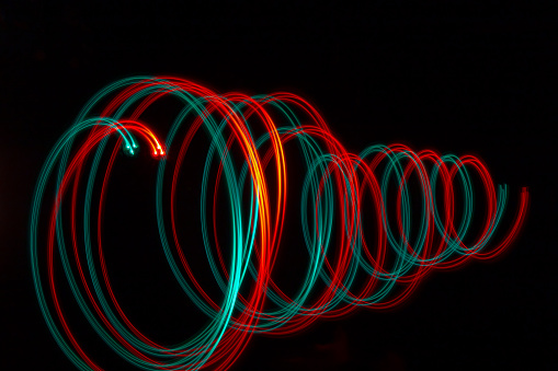 Twirl of red and green colored lights on black background