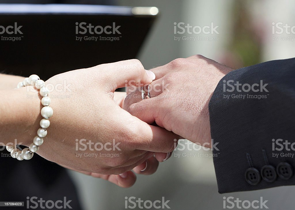 Ring On His Finger A couple exchanging wedding vows and rings on their big day. Authority Stock Photo