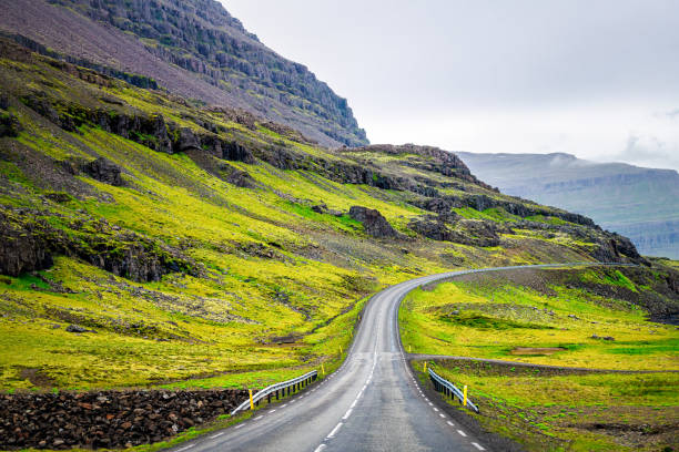 Ring road in east Iceland highway with green summer landscape mountains cliff on cloudy day and nobody empty near Djupivogur stock photo
