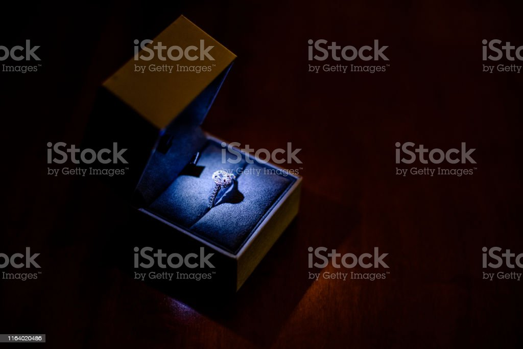Ring with diamonds in its box, focally lit on a black isolated...