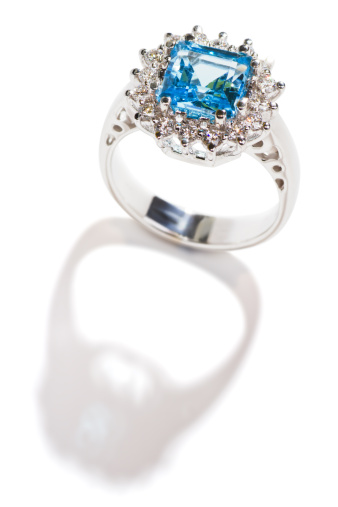 white gold ring with blue topaz and diamonds, isolated on white, with shadow