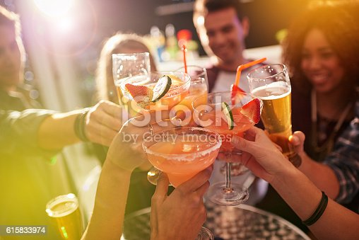 Shot of a group of people toasting with their drinks at a nightclub