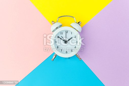1139289535 istock photo Ringing twin bell classic alarm clock isolated on blue yellow pink pastel colorful geometric background. Rest hours time of life good morning night wake up awake concept. Flat lay top view copy space 1209866733