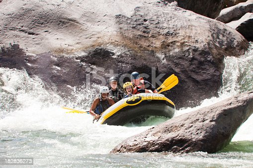Group of excited friends scream while running whitewater rapids in inflatable raft. Rio Cangrejal, Honduras