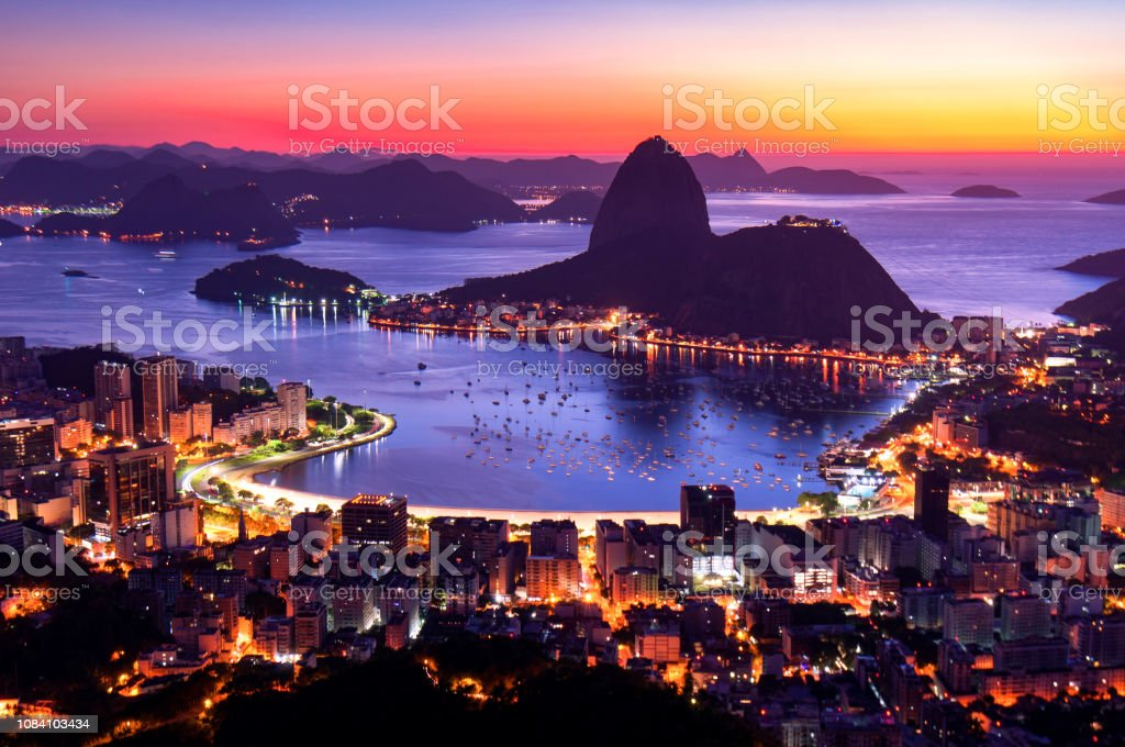 Rio de Janeiro by Sunrise Rio de Janeiro just before Sunrise, City Lights, and Sugarloaf Mountain. Bay of Water Stock Photo