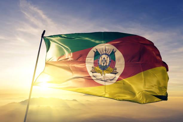 Rio Grande do Sul state of Brazil flag textile cloth fabric waving on the top sunrise mist fog stock photo