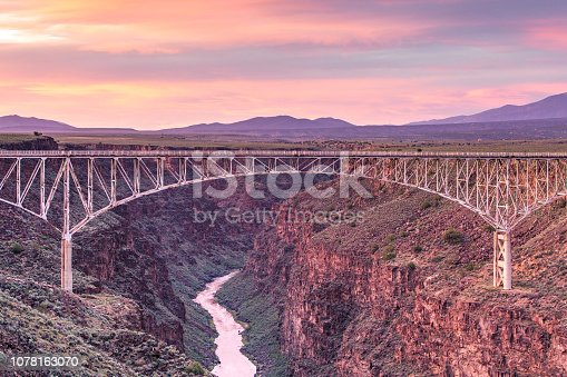 A colorful sky forms the backdrop to the bridge spanning the Rio Grande Gorge near Taos, New Mexico.