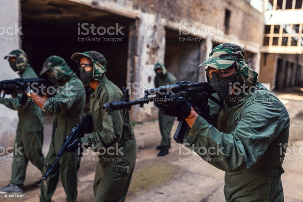 Riot army with guns and rifles attacking enemies stock photo