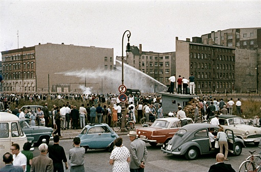 Checkpoint Charlie, Berlin (West), 1961. Ten days after East Berlin was closed (Soviet zone) to the West,  angry West Berliner tried to hinder the construction of the Berlin Wall. They are prevented by water cannons from the East Berlin border troops. Refugees were shot. Furthermore: spectators, parked cars, border facilities and buildings.