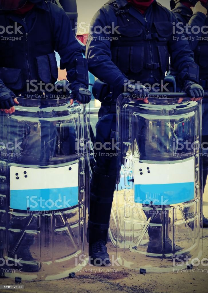 riot cops with batons and shields during security checks through the streets with vintage effect stock photo