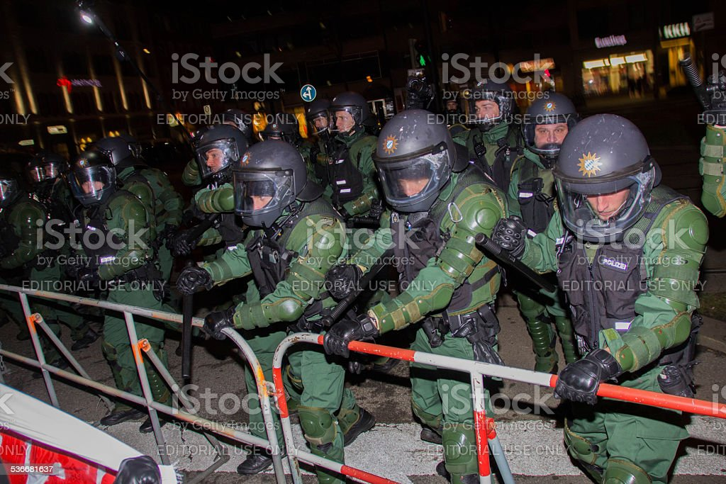 Riot Police behind barriers confronting left-wing protesters stock photo