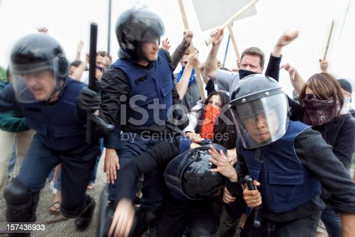 Riot Police Fight Angry Mob. This stock image has a horizontal composition.