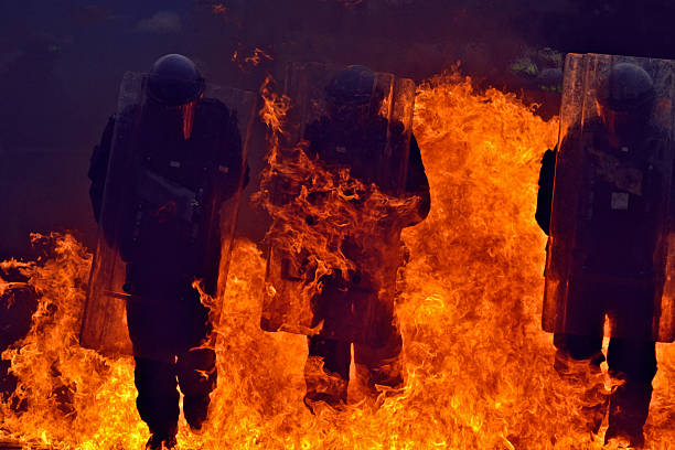 UK Riot Police Flames UK Riot Police run through flames riot police stock pictures, royalty-free photos & images