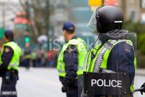Riot police stand on high alert during protest.