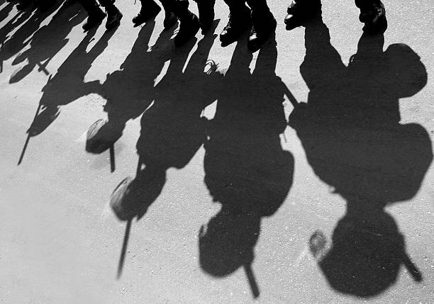 Riot Police Shadows of riot police on a city street. riot stock pictures, royalty-free photos & images