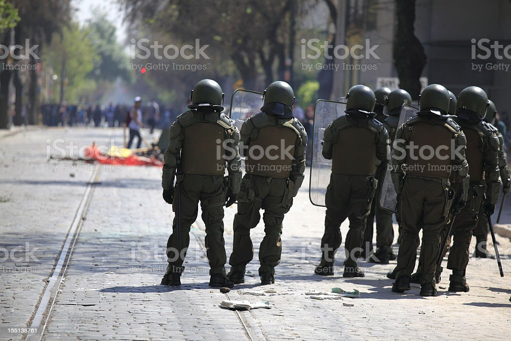 Riot police with a mob in the background stock photo