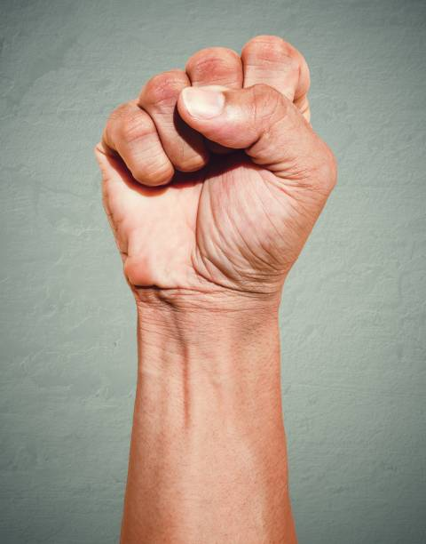 riot protest fist raised in the air. male clenched fist on dark grunge background. - fist stock photos and pictures