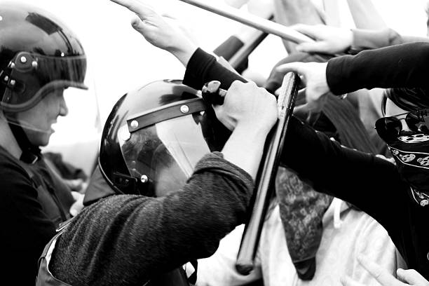 rioting police action close up and personal view   inside a riot with police action. photo journalistic style black and white with grain.  riot police stock pictures, royalty-free photos & images