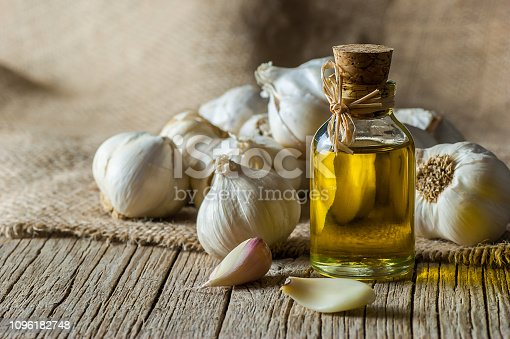 Ripe and raw garlic and garlic oil in glass of bottle on wooden table with burlap sack, alternative medicine, organic cleaner. Garlics background
