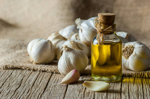 ripe and raw garlic and garlic oil in glass of bottle on wooden table with burlap sack, alternative medicine, organic cleaner. garlics background - aglio alliacee foto e immagini stock