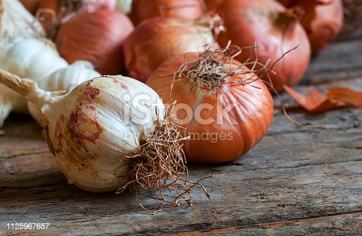 Ripe and raw onion and garlic on wooden background, alternative medicine, organic cleaner. Onions and garlics background