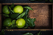 ripe and refreshing lime fruits in wooden crate, fresh from local market