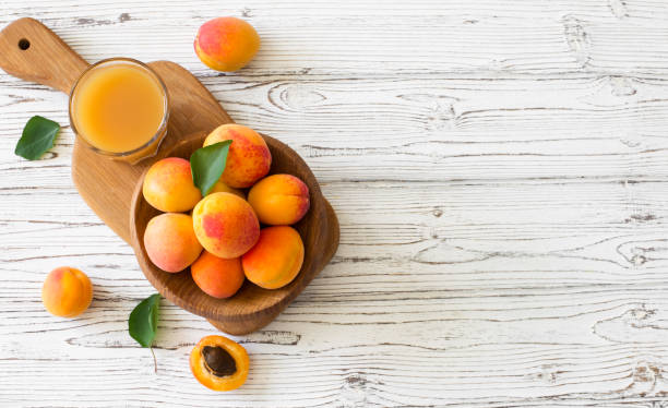 Ripe apricots and glass of juice in wooden bowl stock photo