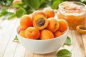 istock Ripe apricots with leaves in a white ceramic bowl on a light table. Apricot jam. 1180157986