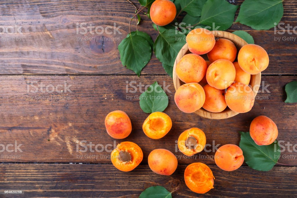ripe apricots with leaves in a wooden plate on a wooden background. royalty-free stock photo