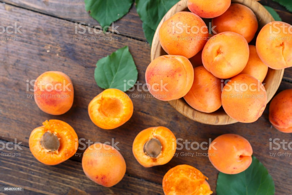 ripe apricots with leaves in a wooden plate royalty-free stock photo