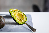 Ripe avocado cut on gray cutting board. Minimalism food photography concept. Copy space