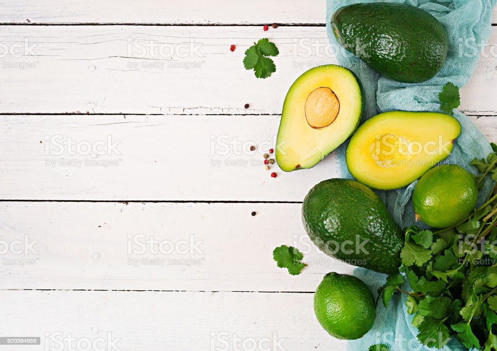 Reife Avocado, Limette und Koriander auf einem Leuchttisch aus Holz. Gesunde Ernährung-Konzept. Ansicht von oben – Foto