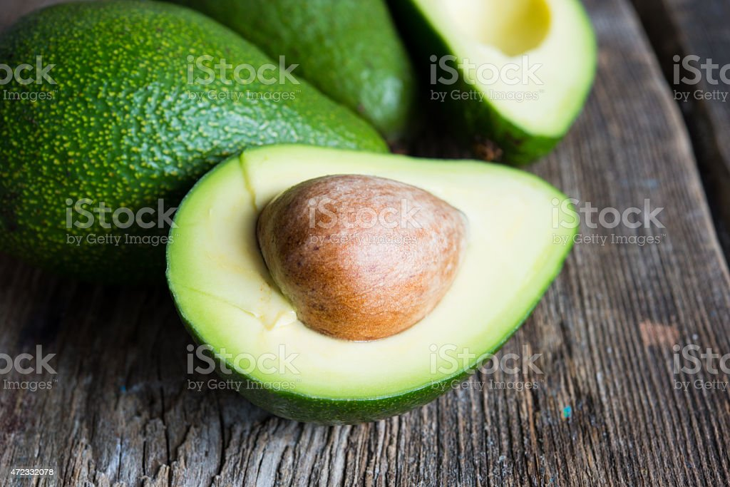 Ripe avocado on a wooden background stock photo
