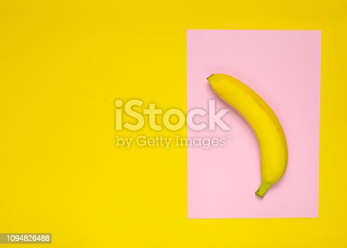 Ripe banana on a pink yellow background. Top view. Minimalism
