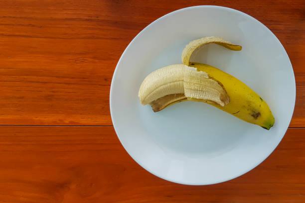 reife banane auf teller weiß lag auf dem holzboden. - bananeneis stock-fotos und bilder