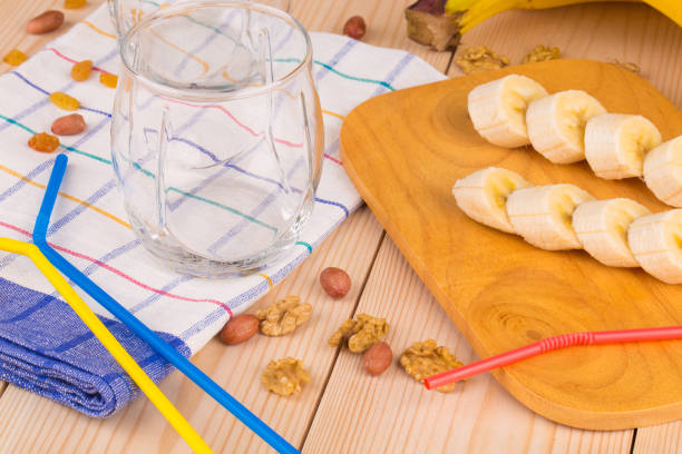 Ripe bananas and empty glasses on tablecloth. stock photo
