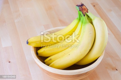 Bunch of bananas in a wooden bowl on a table.