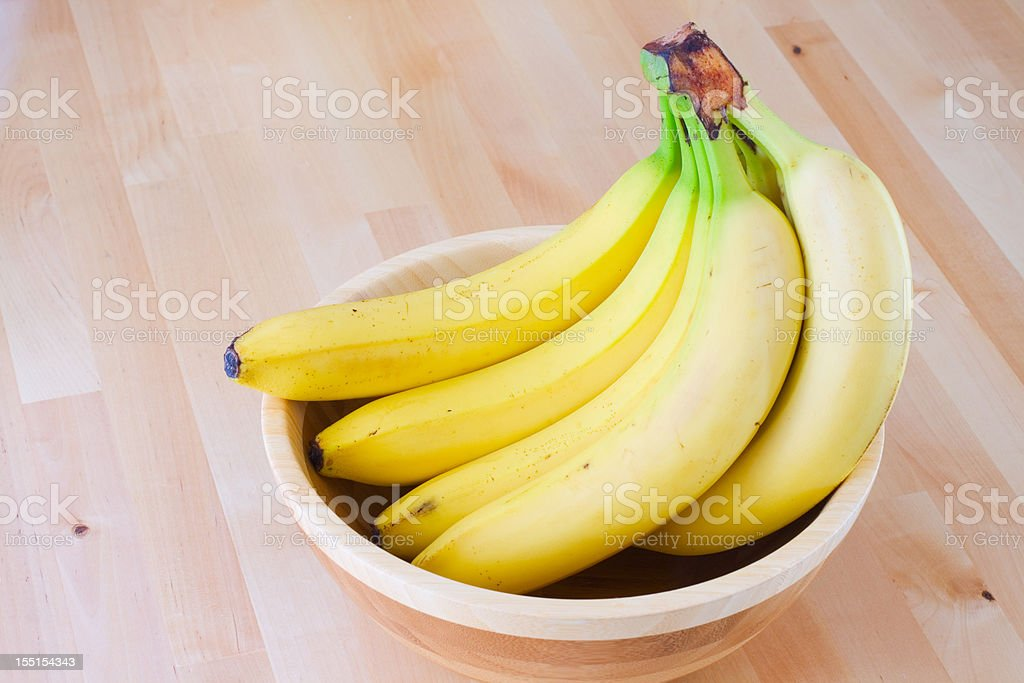 Ripe bananas in a wooden bowl stock photo