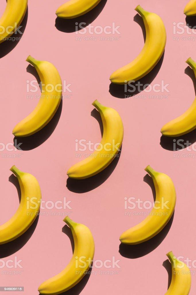 Ripe bananas on pink surface stock photo