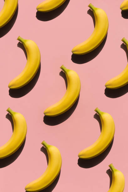 Ripe bananas on pink surface stock photo