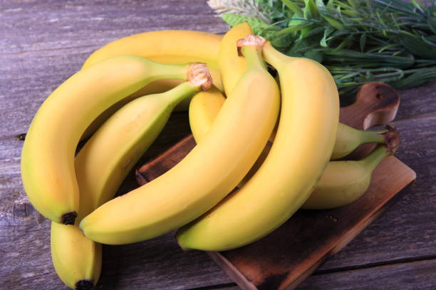 Ripe bananas on wooden table stock photo