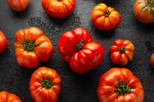 Ripe Beefsteak Tomatoes on rustic black table.