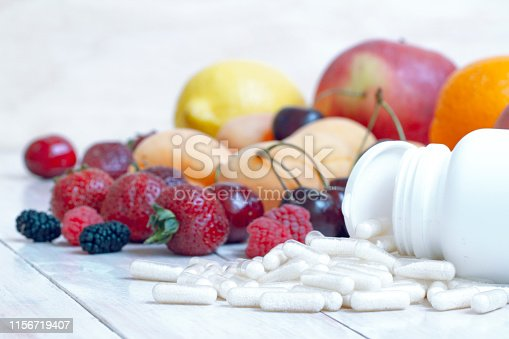 istock Ripe berries. Vegetarian food. Nutritional supplements. Fresh vitamin nutrition. Natural food. Detox diet. Body care. capsules and tablets of vitamins with berries and fruit. Fresh fruit. 1156719407